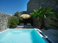 Secluded pool area between stone walls with blue and white striped sun loungers, straw parasol and palm tree