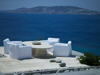 Loose-covered chairs and stone table on exposed, high terrace directly be the sea