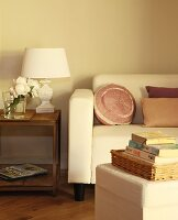 Stacked books on stool opposite sofa with elegant scatter cushions next to vintage-style table lamp with white lampshade on wooden side table