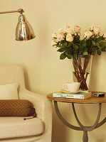 Glass vase of roses on delicate side table next to armchair; partially visible retro, chrome standard lamp