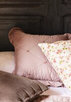 Various pillows in pink, brown and floral pattern