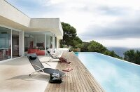 Contemporary holiday home with projecting flat roof; sun loungers on wooden deck next to infinity pool