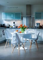 Modern kitchen with white cupboards and Tulip table and chairs in centre