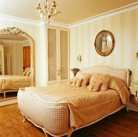Cream bedroom in English country house with full-length mirror on wall, crystal chandelier and comfortable double bed with fur scatter cushions