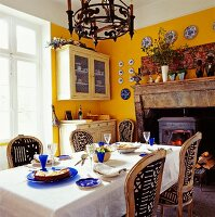 Antique fireplace with wood-burning stove in yellow dining room of French country house; dining table set with blue glasses and plates in foreground