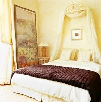 Grand bed with canopy and dark brown fur blankets in cream bedroom