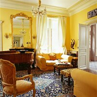 Grand living room with yellow-upholstered furniture, gilt-framed mirror, grand piano and huge Persian rug