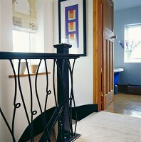 Head of staircase with wrought iron balustrade and view into blue bedroom