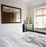Bright bedroom with antique furniture and large, rectangular mirror on wall; white dressing gown on bed