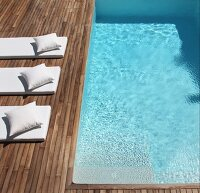 Pale futon loungers with matching cushions on wooden deck adjoining pool