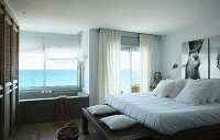 Double bed with white bed linen and bathtub below window with panoramic sea view