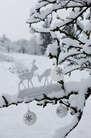 Two wooden deer figurines and white Christmas baubles on snow-covered branch