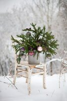 Spruce branches decorated with Christmas baubles on shabby-chic chair in snowy landscape