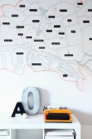 Stylised, string-art map of city decorating wall, orange retro typewriter and ornamental letter on white shelf