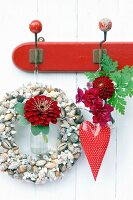 Wreath of seashells, metal heart, zinnia, dahlia and snap dragon hung on vintage coat rack