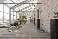 Converted greenhouse with wooden decking and exposed brick wall