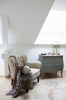Antique armchair next to wooden chest of drawers in bright attic room