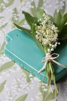 Lily of the valley on green ceramic panel on tablecloth with lily of the valley pattern