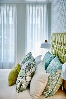 Green patterned scatter cushions on double bed with button-tufted headboard in front of white curtains