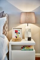 Table lamp with sculptural base on white retro bedside cabinet with bookshelf
