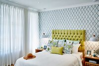 Bedroom with double bed, yellow upholstered headboard, scatter cushions and retro wallpaper