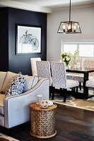 Cylindrical, hand-crafted side table next to sofa, dining area with patterned upholstered chairs around table and framed picture on black accent wall