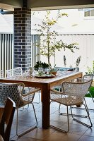 Classic-style mesh chairs around wooden table on roofed terrace