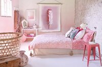 Pink metal stool next to double bed with patterned bedspread and wall hanging with picture of pink feather in pink, retro bedroom