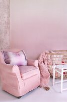 Armchair, cushion and wicker laundry basket against pink-painted wall in corner