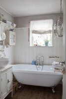 Vintage claw-foot bathtub against wood-clad wall in white bathroom