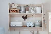 Pastel shabby-chic crockery and food stored in vintage-style jars and bottles on wall-mounted kitchen shelves