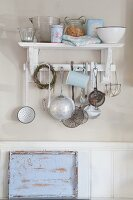 Vintage kitchen utensils hanging from hooks below bracket shelf and sky-blue, shabby-chic tray leaning against wainscoting