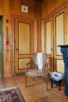 Rococo-style chairs in corner in front of fitted cupboards with painted doors