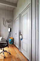 Modern office chair on rustic wooden floor in room with wooden walls painted pale grey