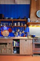 Kitchen counter with solid wooden base units below blue-painted wooden wall