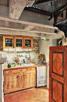 Solid wooden kitchen cabinets on stone walls in vintage-style interior