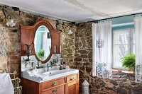 Solid wooden washstand with mirror in corner of rustic bathroom with stone walls