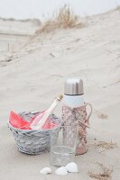 Beach picnic with thermos flask in pink crocheted cover