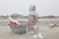 Thermos flask with pink crocheted cover for beach picnic