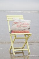 Cushion with crocheted seagull motif on wooden chair on beach