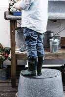 Boy standing on upturned zinc tub at potting bench on balcony