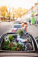 Urban gardening: young woman in convertible car with foliage plants and vegetable plants