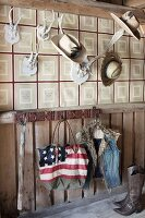 Stars and stripes bag and waistcoat hanging from wall hooks below various hats on antlers on wallpapered wall