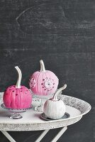 Ornamental squashes painted pink and white decorating table