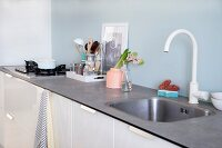 White kitchen counter with pale blue splashback, vase and kitchen utensils