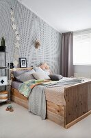 Collection of scatter cushions on rustic wooden bed against wallpapered wall