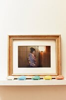 Framed photo of geisha behind toy cars of various colours on shelf