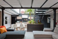 Sofas in open-plan interior with double-height dining area and steel staircase