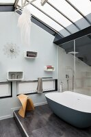 Bathroom with glass roof and designer bathtub on platform