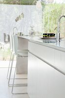 Elegant white kitchen island with bar stools